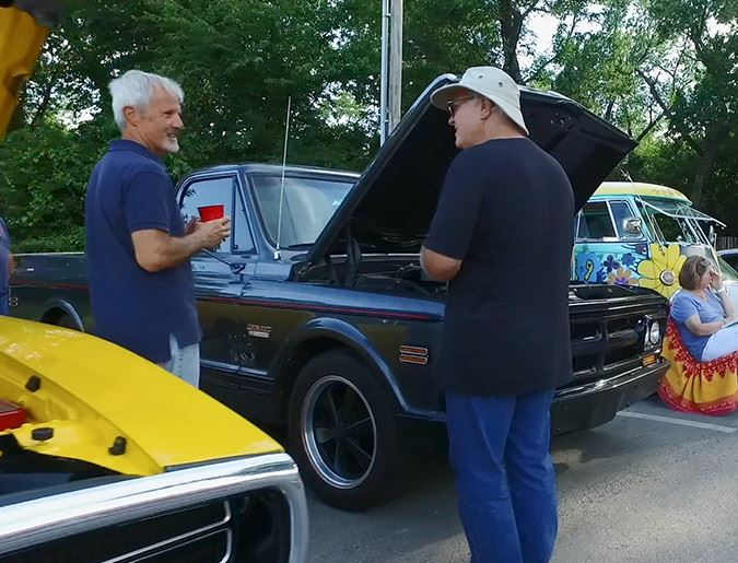 men talking at a car show outdoors